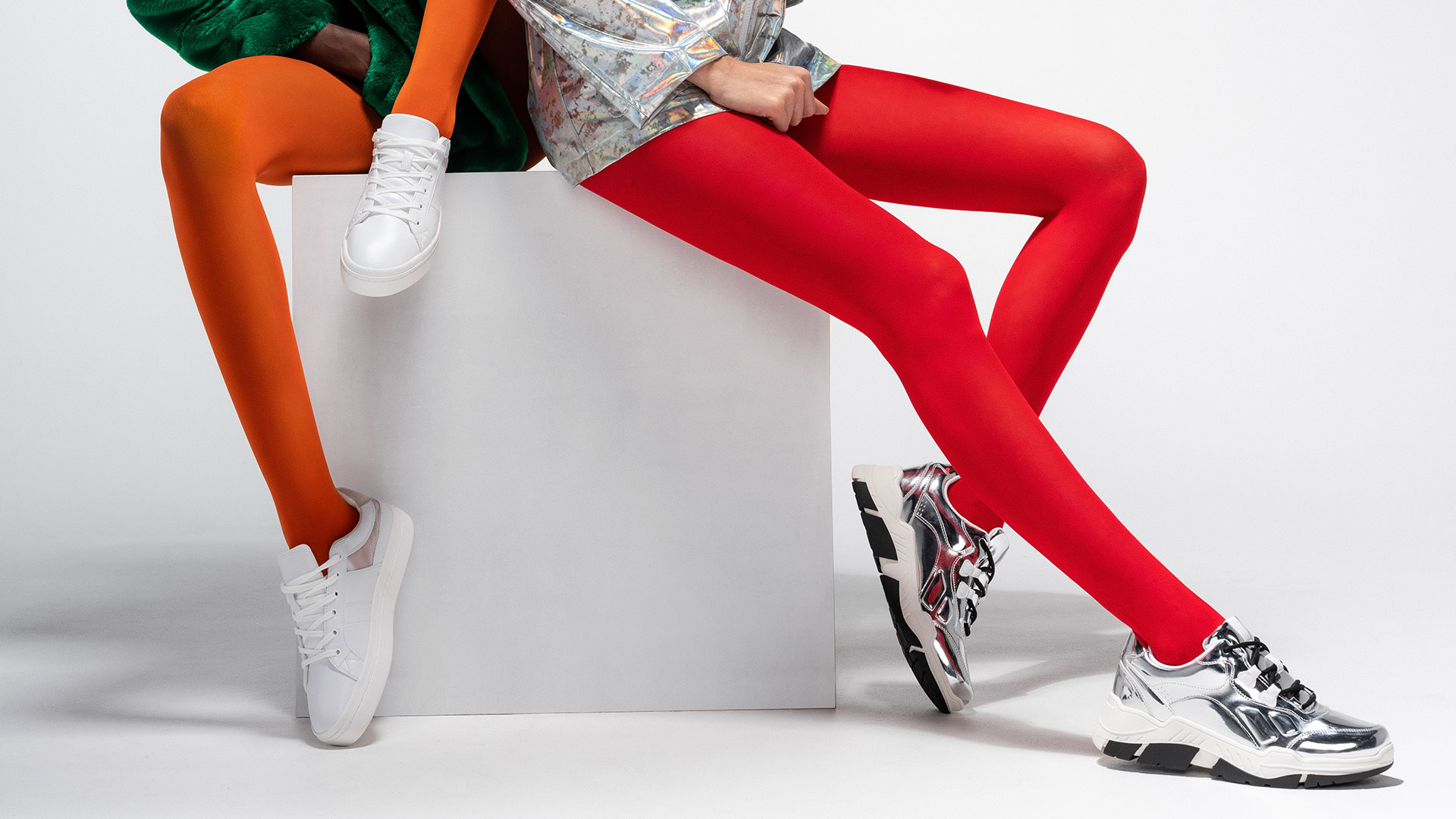 two ladies wearing Fogal tights Opaque rouge and Opaque orange